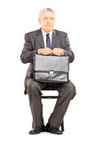 Mature businessman in suit holding a briefcase and waiting Stock Photos