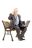 Mature businessman in suit sitting and talking on a phone Stock Photography