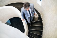 Businessman with suitcase walking down the stairs. Stock Photos