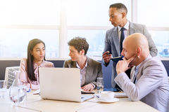 Mature businessman supervising his employees as they work royalty free stock photos