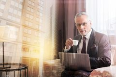 Mature businessman taking break and drinking coffee. Recharging my batteries. Confident male entrepreneur looking into the camera while sitting with a laptop on Royalty Free Stock Photo