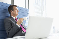 Mature businessman taking coffee break in office Royalty Free Stock Photo