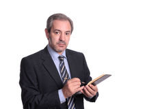 Mature businessman taking notes. Isolated on white Royalty Free Stock Photos
