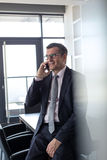 Mature businessman talking on mobile phone in board room Stock Images