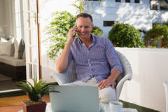 Mature businessman talking on phone while sitting outdoor cafe Stock Image