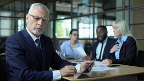 Mature businessman thinking of decision looking tablet, managers discussing plan