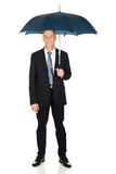 Mature businessman with umbrella Royalty Free Stock Images