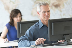 Mature Businessman Using Computer In Office Royalty Free Stock Photos
