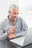 Mature businessman using laptop at office desk Royalty Free Stock Photo