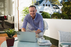 Mature businessman using laptop while sitting at outdoor cafe Royalty Free Stock Photo