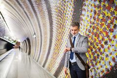 Mature businessman waiting on a metro station. Handsome mature businessman in a city. Man waiting for the train at the subway station, checking times Royalty Free Stock Photo