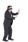 Mature businessman walking with blindfold Stock Image