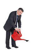 Mature businessman watering with red can Stock Photography