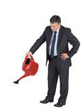 Mature businessman watering with red can Royalty Free Stock Photos