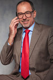 Mature businessman wearing glasses smiling. Confident mature businessman wearing glasses smiling while calling on his smartphone and looking at the camera in Royalty Free Stock Images