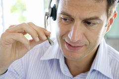Mature businessman wearing headset, close-up Stock Photo