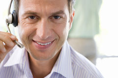 Mature businessman wearing headset, hand on microphone, smiling, portrait, close-up Royalty Free Stock Photo