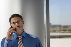 Mature businessman wearing spectacles, using mobile phone beside window, front view Stock Image