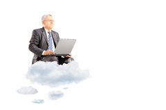 Mature businessman wearing suit and flying on clouds with laptop Stock Images