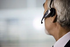 Mature businessman wearing telephone headset, side view, close-up Royalty Free Stock Photos