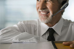 Mature businessman wearing telephone headset, smiling, close-up Royalty Free Stock Images