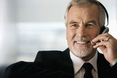 Mature businessman wearing telephone headset, smiling, front view, close-up, portrait Royalty Free Stock Images