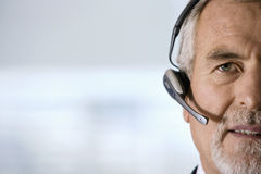 Mature businessman wearing telephone headset, talking, front view, close-up Stock Photography