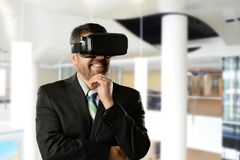 Mature Businessman wearing Virtual Reality Goggles. Inside an office building Stock Photos