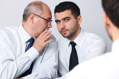Mature businessman whisper something to colleague. Mature businessman whisper something to his younger colleague during interview, privacy concept Stock Photo