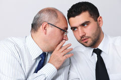 Mature businessman whisper something to colleague. Mature businessman whisper something to his younger colleague, privacy, secret concept Royalty Free Stock Image