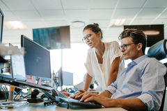 Mature businessman working on computer with colleague. Mature businessman working on desktop computer with asian female colleague. Two office worker working Royalty Free Stock Photos