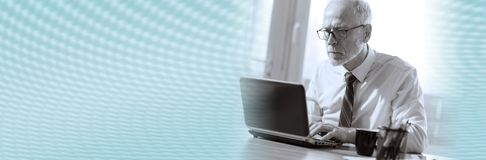 Mature businessman working on laptop, black and white; panoramic banner royalty free stock photo