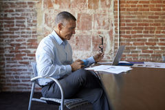 Mature Businessman Working On Laptop In Boardroom Stock Image