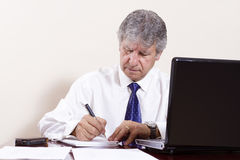 Mature businessman working with laptop in his office Royalty Free Stock Photos
