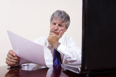 Mature businessman working with laptop in his office Royalty Free Stock Images