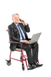 Mature businessman working on laptop in a wheelchair Stock Photography
