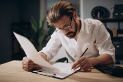 Mature businessman working late with financial documents. Mature businessman in eyeglasses and formal outfit working with financial documents at own office with