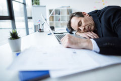 Mature businessman at workplace. Mature businessman in suit sleeping at table with laptop and papers Royalty Free Stock Photo