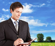 Mature businessman writing. Something on his agenda outdoor Stock Images