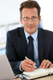 Mature businessman writing appointments in agenda Royalty Free Stock Images