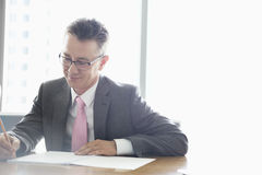 Mature businessman writing on book at table in office Royalty Free Stock Image