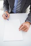Mature businessman writing on document Stock Images