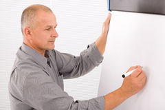 Mature businessman writing at empty flip chart Royalty Free Stock Photos