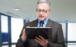 Mature businessman writing on his agenda Royalty Free Stock Photography