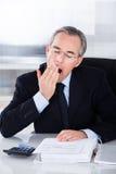 Mature businessman yawning Stock Photos