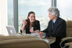 Mature businessman and young business woman discussing Stock Image