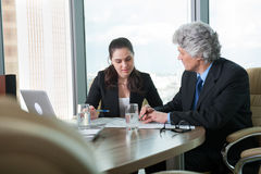 Mature businessman and young business woman discussing Royalty Free Stock Images