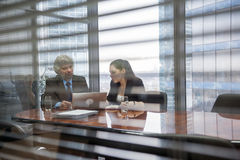 Mature businessman and young business woman discussing Stock Images