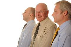 Mature businessmen. Side view of three mature businessmen, with one in centre smiling; white background Royalty Free Stock Photography