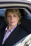 Mature businesswoman in back of car, smiling, portrait Stock Images